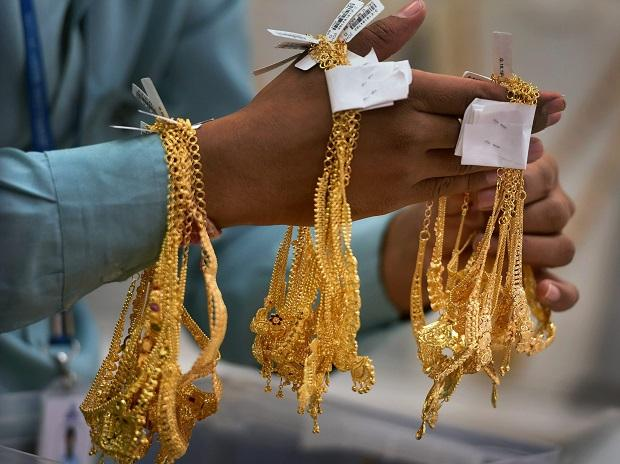 A sales person shows gold ornaments at a jewellery shop, on the occasion of